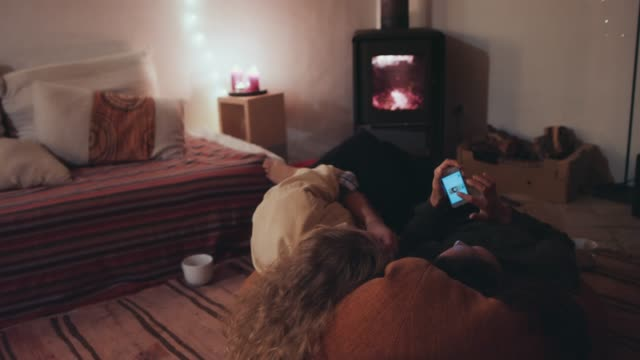 stockvideo's en b-roll-footage met two young women lying on cushion, looking at smart phone in front of fireplace - open haard