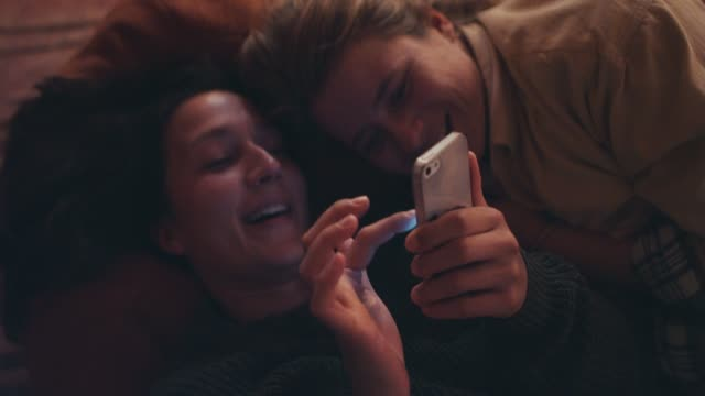 stockvideo's en b-roll-footage met two young women lying on cushion, looking at smart phone, snuggling - aanhankelijk