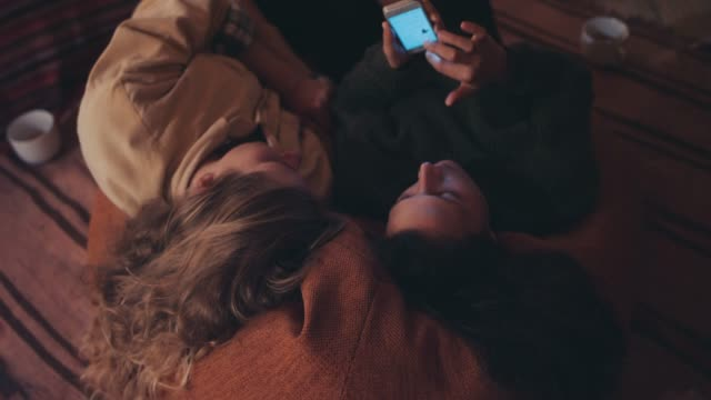 two young women lying on cushion, looking at smart phone - messaggistica online video stock e b–roll
