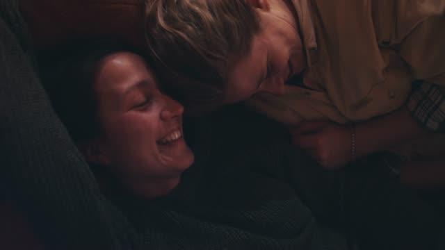 vídeos de stock e filmes b-roll de two young women lying on cushion, snuggling, talking, laughing - rir
