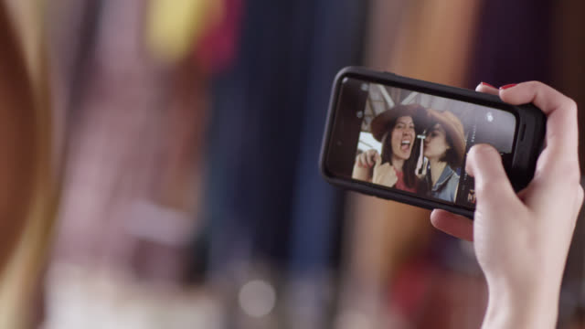 vídeos de stock, filmes e b-roll de two young women make funny faces and take selfies with smartphone - celular com câmera