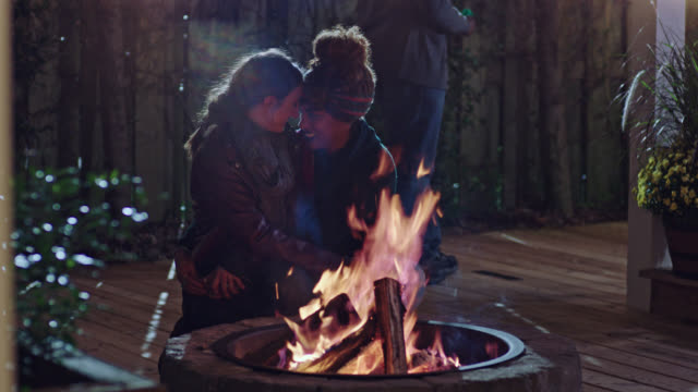 stockvideo's en b-roll-footage met two young women nuzzle and embrace beside fire pit. - eskimokus geven