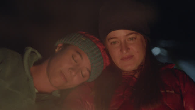 Two young women on camping trip lean on each other and watch the flickering light of the campfire.