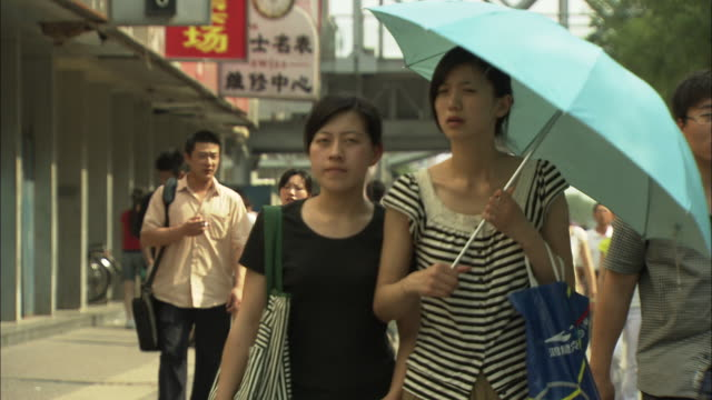 ms two young women on crowded sidewalk in xidan shopping district, beijing, china - pavement video stock e b–roll