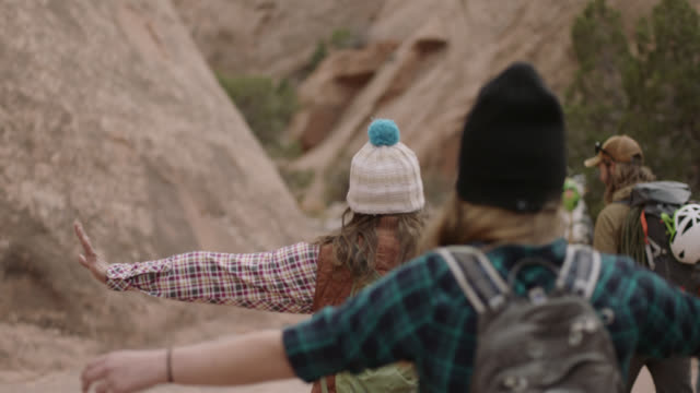 vídeos de stock, filmes e b-roll de two young women on hiking trip with friends walk with arms out for balance on rocky moab trail. - cultura jovem
