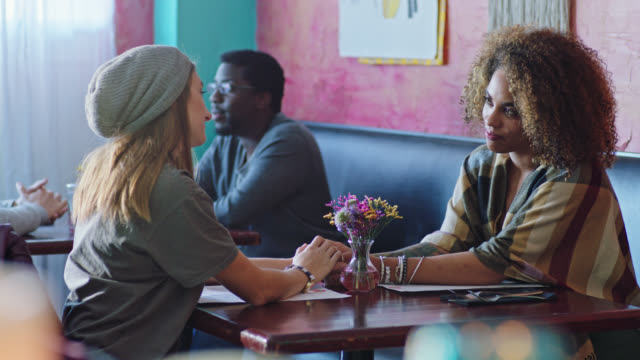 Two young women on lunch date hold hands across the table and gaze at each other.