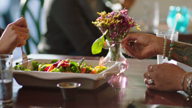 vídeos y material grabado en eventos de stock de two young women on lunch date share delicious salad. - comida sana