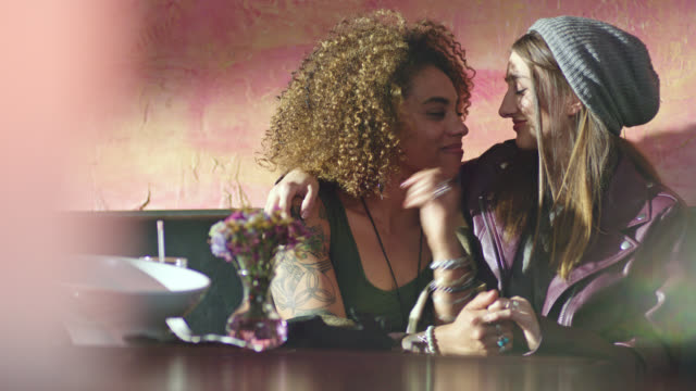 two young women on lunch date share kiss at restaurant table. - verlieben stock-videos und b-roll-filmmaterial