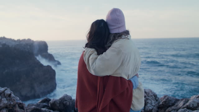 vídeos de stock, filmes e b-roll de two young women on sea cliffs looking out at waves - um do lado do outro