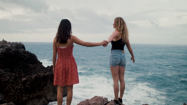 two young women on sea cliffs looking out at waves - imperfection stock videos & royalty-free footage