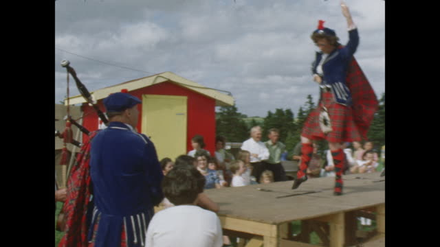 Two young women performs a Highland dance on stage in front of the festival crowd dancing over crossed swords man plays bagpipes