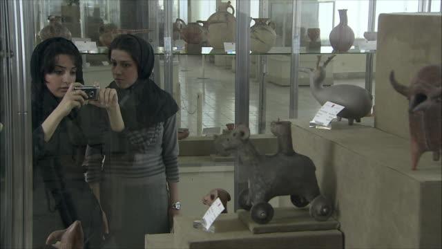 ms two young women photographing ancient pottery vessels in national museum of iran, tehran, iran - skåp med glasdörrar bildbanksvideor och videomaterial från bakom kulisserna