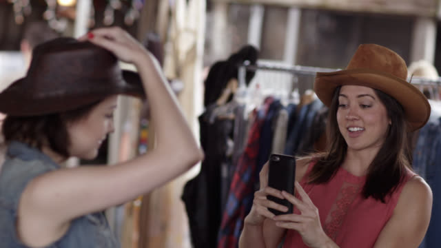 two young women pick out cowboy hats and take smartphone photo in western store - flea market stock videos and b-roll footage