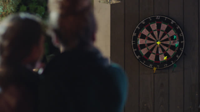 two young women play darts on back patio. - darts stock videos and b-roll footage