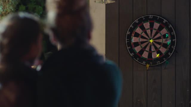 two young women play darts on back patio. - ダーツバー点の映像素材/bロール