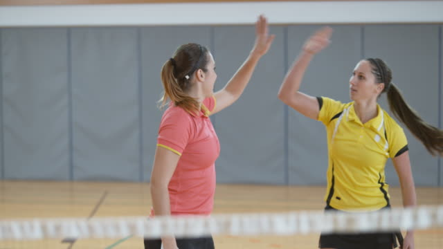 Two young women playing doubles in indoor badminton