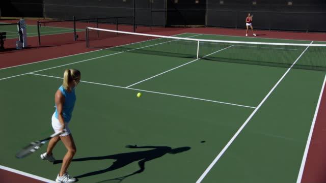 vidéos et rushes de ws, cs, two young women playing tennis, santa barbara, california, usa - terrain de jeu