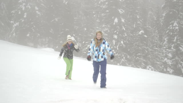 two young women playing with snow - skijacke stock-videos und b-roll-filmmaterial