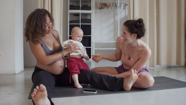 vídeos de stock e filmes b-roll de two young women playing with their son in a yoga studio - família com um filho