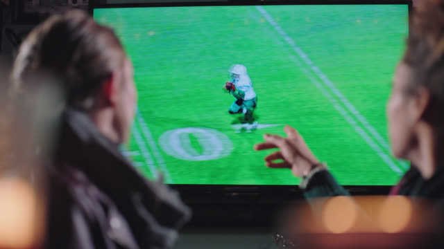 Two young women point and laugh while watching football on big screen tv in sports bar.