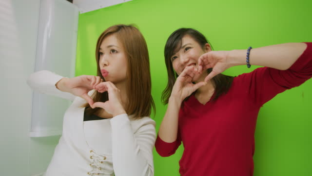 MS Two young women pose in a photo booth / Tokyo, Japan