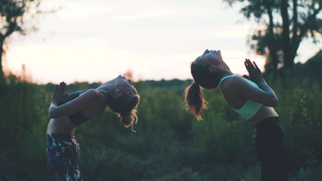 Two young women practicing yoga, laughing together at sunrise in the forest in the South of France.