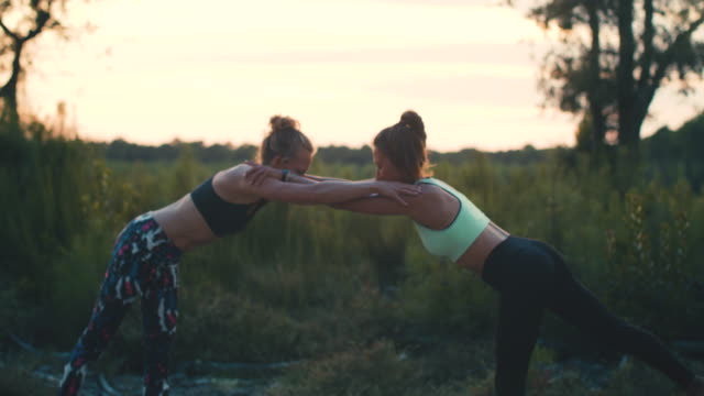 vídeos de stock, filmes e b-roll de two young women practicing yoga together at sunrise in the forest in the south of france. - sutiã para esportes