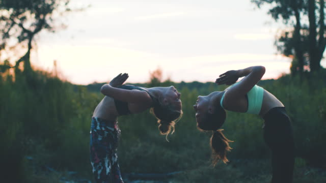 Two young women practicing yoga together at sunrise in the forest in the South of France.