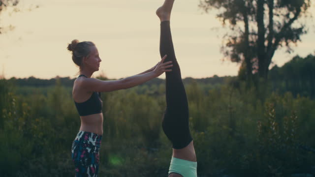 Two young women practicing yoga/handstand/doing high fives together at sunrise in the forest in the South of France.