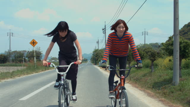 two young women riding bicycles in a rural area - サイクリング点の映像素材/bロール
