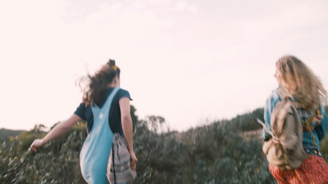two young women running with backpacks up hill in portugal - 避ける点の映像素材/bロール