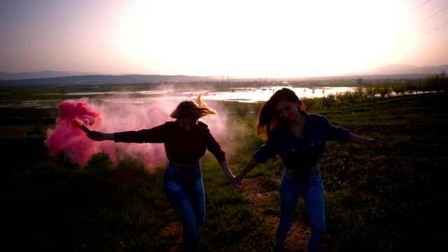 Two young women runs and spins around with a pink smoke grenade, slow motion