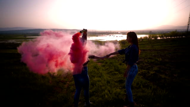 two young women runs and spins around with a pink smoke grenade, slow motion - flaming torch stock videos & royalty-free footage