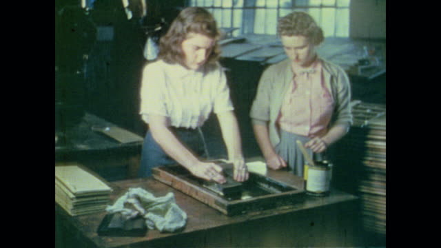 vidéos et rushes de two young women screen-print signs by hand - 1942