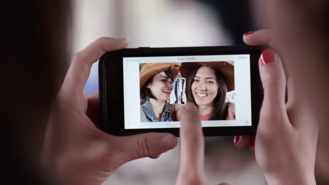 Two young women scroll through cute selfies on smartphone