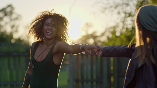 SLO MO. Two young women share a passionate dance in their backyard.