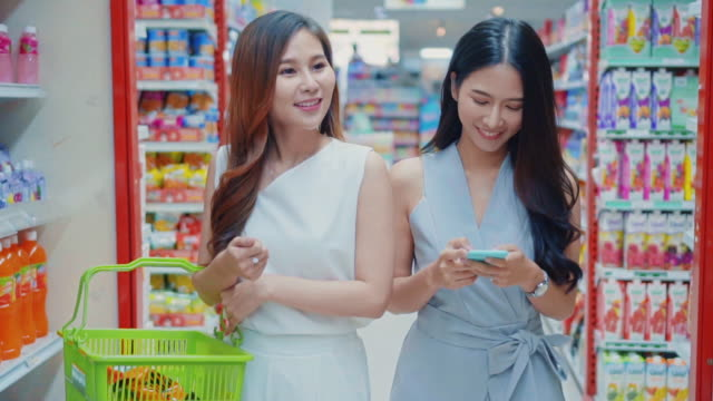 two young women shopping and using smartphone in supermarket,slow motion - shelf stock videos & royalty-free footage