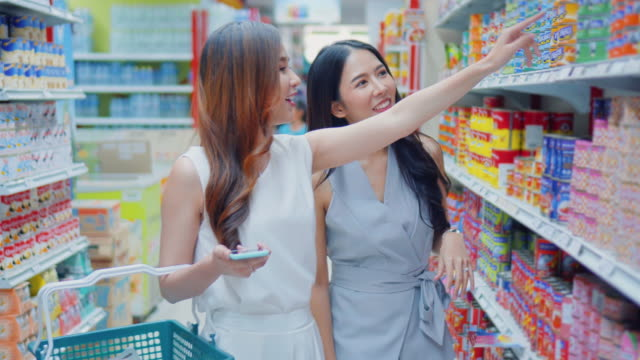 two young women shopping in supermarket - consumerism stock videos and b-roll footage