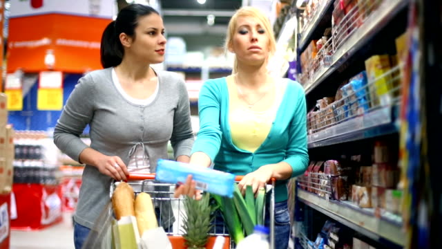 two young women shopping in supermarket. - cart stock videos & royalty-free footage