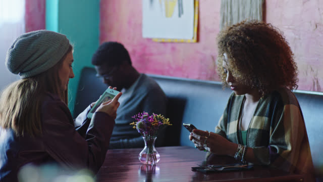 two young women sit and look at smartphones in local cafe. - dipendente video stock e b–roll