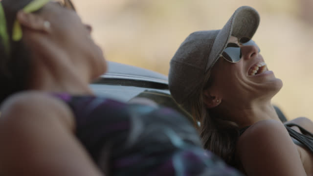 Two young women sit on hood of car and talk on Moab road trip.