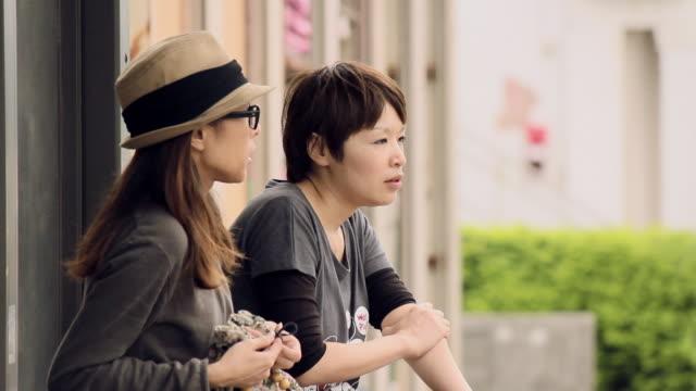 ms two young women sitting and talking at bus stop / kin, okinawa, japan   - バス停留所点の映像素材/bロール