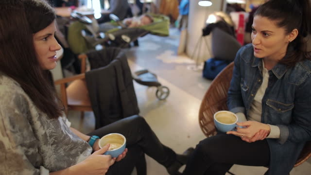 Two young women sitting at a coffee table.