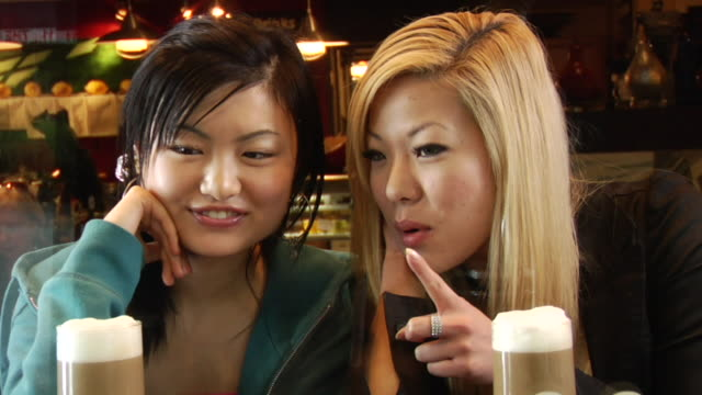 ms two young women sitting at coffee shop coffee shop window, talking, smiling, and pointing/ vancouver, bc - see other clips from this shoot 1100 stock videos & royalty-free footage