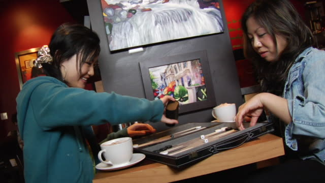 vídeos de stock e filmes b-roll de ms td canted two young women sitting at table in coffee shop and playing backgammon beneath painting and faith sign/ vancouver, bc - kelly mason videos