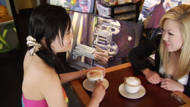 hs ms two young women sitting at table in coffee shop drinking cappuccino/ women looking up at camera/ vancouver, bc - see other clips from this shoot 1100 stock videos & royalty-free footage