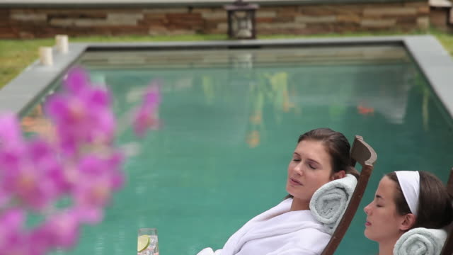 ms td two young women sitting beside pool at spa resort / richmond, virginia, usa - spa treatment stock videos & royalty-free footage