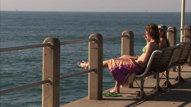 ws two young women sitting on bench on pier looking at ocean / durban, kwazulu-natal, south africa  - badebekleidung stock-videos und b-roll-filmmaterial
