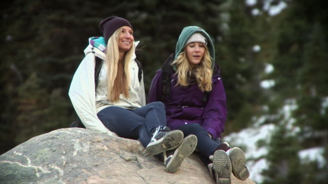 ws tu two young women sitting on large rock on whistler mountain / whistler, british columbia, canada  - legs crossed at ankle stock videos and b-roll footage