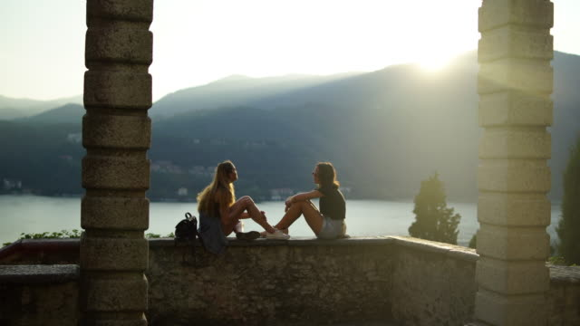 two young women sitting on stone wall framed by pillars overlooking lake and mountains - surrounding wall stock videos & royalty-free footage